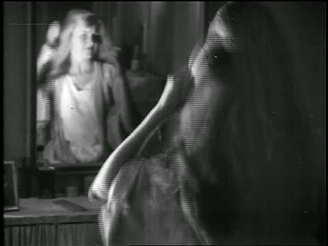 vidéos et rushes de b/w 1920s young woman brushing long hair in mirror / educational - miroir