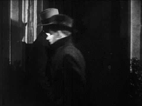 b/w 1920s zoom in man knocking on door of speakeasy is denied entrance / prohibition / newsreel - 禁酒法点の映像素材/bロール