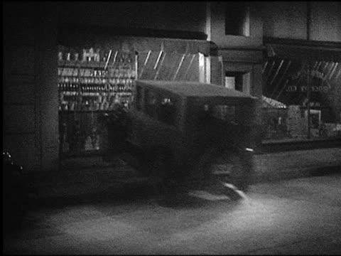B/W 1920s/30s car crashing into store at night / crowd gathers