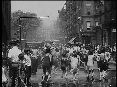 vidéos et rushes de b/w 1920s/30s children jumping up + down in spray of fire hydrant in city street - 1930