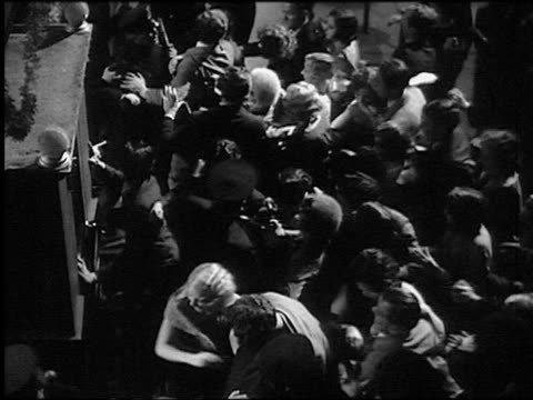 b/w 1920s/30s high angle angry crowd rushing police line / police pushing them back - mob stock-videos und b-roll-filmmaterial