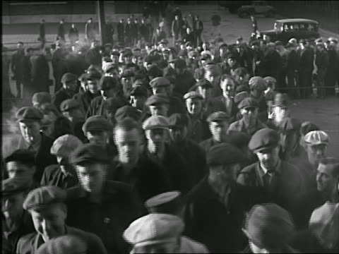 stockvideo's en b-roll-footage met b/w 1920s/30s high angle male blue collar workers in caps walking towards camera to enter factory - 1930