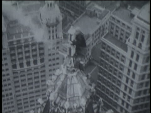 b/w 1920s/30s man climbing onto top of spire of woolworth building / nyc - woolworth building stock videos & royalty-free footage