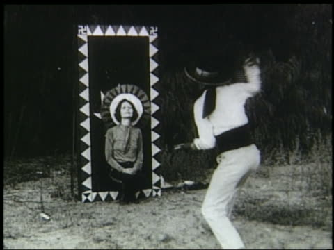 B/W 1920s/30s man with cowboy hat throwing knives at kneeling woman against wall
