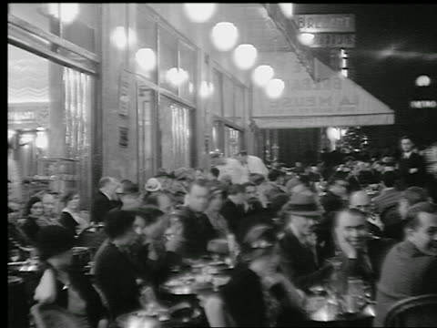 b/w 1920s/30s people at tables in crowded sidewalk cafe at night / paris, france - 1930 stock videos and b-roll footage