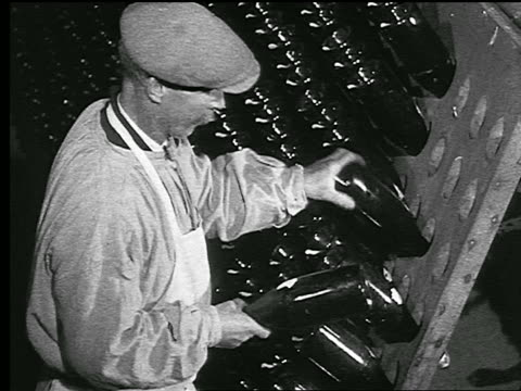 b/w 1920s/30s profile man shaking bottles + inserting them into rack in champagne cave / reims, france - champagne stock videos & royalty-free footage
