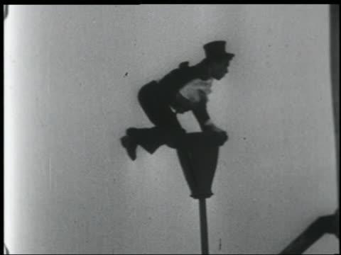 B/W 1920s/30s SIDE VIEW wacky man in formalwear on swaying pole on edge of roof / NYC