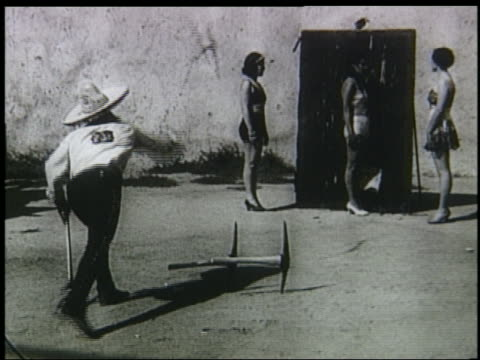 B/W 1920s/30s slow motion man with sombrero throwing pickaxes at woman in bikini against wall