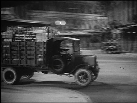 b/w 1920s/30s pan truck full of produce crashing into parked car on city street / man falls in foreground - 1930 stock-videos und b-roll-filmmaterial