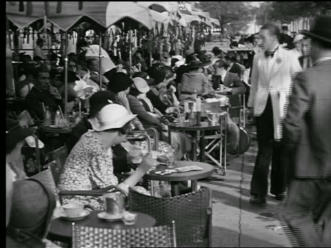 b/w 1927crowded sidewalk cafe with people eating at tables + waiters walking by / paris, france - 1920 stock videos & royalty-free footage