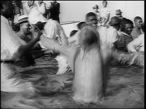 b/w 1930s 2 black men holding arms of baptised man singing + jumping in water - バプテスト点の映像素材/bロール