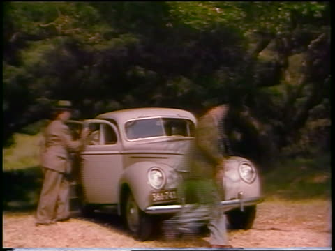 1930s 2 couples getting into ford car in woods / commercial - ford motor company stock videos and b-roll footage