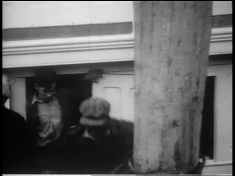 B/W 1930s 2 men handcuffed together climbing from boat / Coast Guard seizing liquor