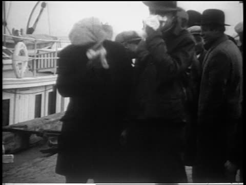B/W 1930s 2 men handcuffed together covering faces with cloths / Coast Guard seizing liquor