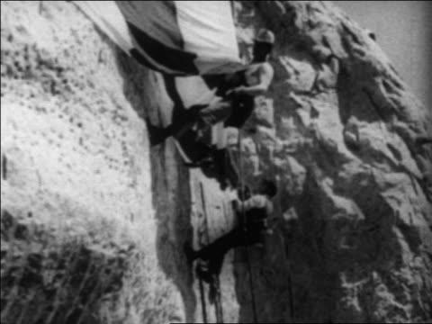 vídeos y material grabado en eventos de stock de b/w 1930s 2 men pulling us flag down side of mt rushmore / south dakota / newsreel - monumento nacional