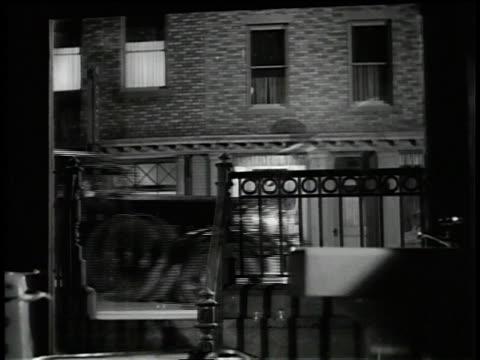 vídeos y material grabado en eventos de stock de 1930s ws a man standing on the running board of a car throws a bottle through a window - estribo de coche