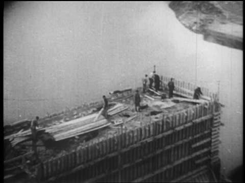vidéos et rushes de b/w 1930s aerial men building dam / tennessee river valley - barrage