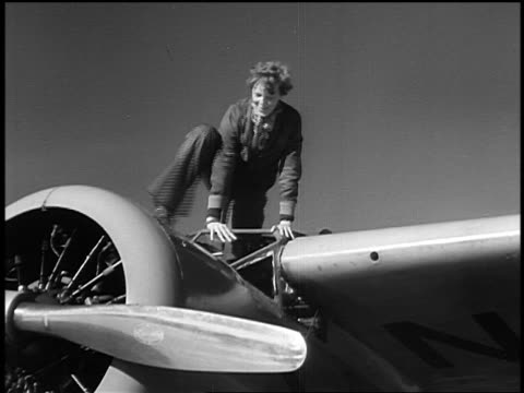 B/W 1930s Amelia Earhart climbing out of airplane