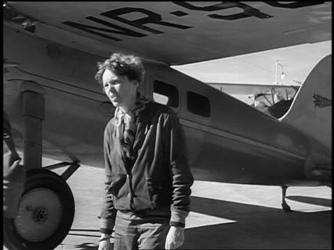 B/W 1930s Amelia Earhart standing by airplane talking