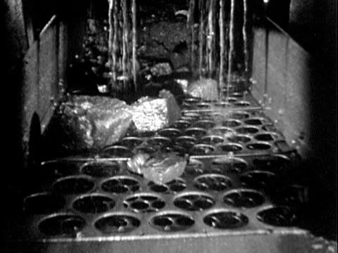 b/w ms 1930s anthracite coal rocks being rinsed with water over shaking screen with various size holes to separate pieces by size, maryland / usa - anthracite coal stock videos & royalty-free footage