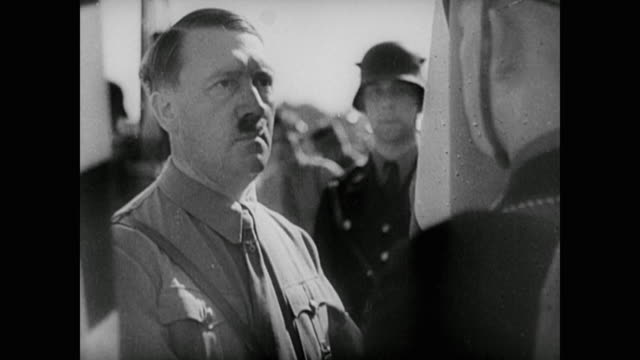 vídeos de stock, filmes e b-roll de 1930s, at a nuremberg rally, adolf hitler moves along a line of nazi military as he holds a nazi flag with one hand and shakes hands somberly with... - adolf hitler