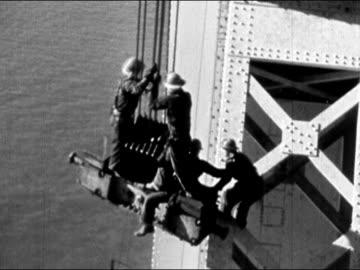 1930s black and white high angle four construction workers riding beam as it swings back and forth / san francisco bay / audio - hängbro bildbanksvideor och videomaterial från bakom kulisserna