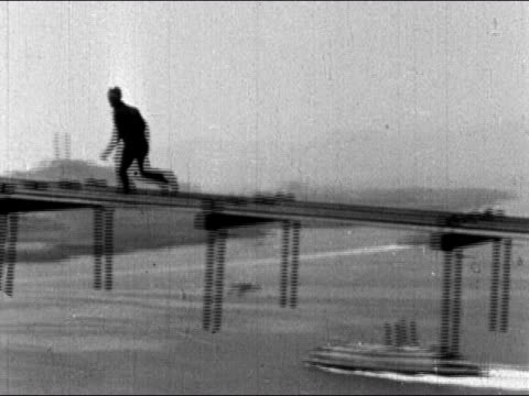 vídeos de stock, filmes e b-roll de 1930s black and white low angle construction worker running along catwalk / san francisco bay / audio - baía de são francisco