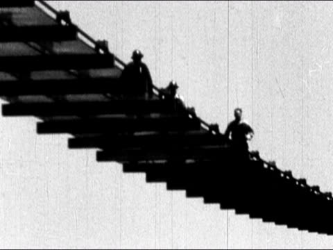 1930s Black and white Low angle construction workers jump up and down on mesh catwalk / San Francisco Bay / AUDIO