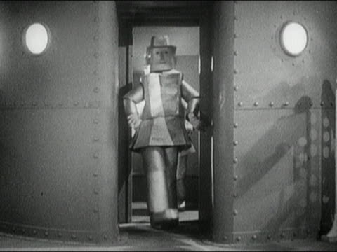 1930s black and white medium shot robots staggering through doorway / one getting stuck in the door / AUDIO