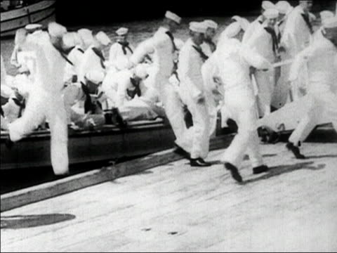 vidéos et rushes de 1930s black and white medium shot sailors jumping off of boat on to dock / hawaii - débarquement