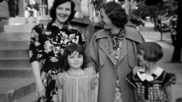 1930s black and white medium shot two women standing behind two young girls / woman playfully pushing heads of girls