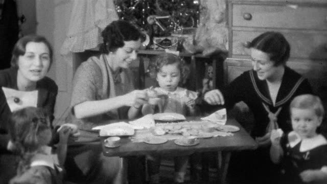 1930s black and white medium shot women and their children having tea party with miniature tea set / long island - svart te bildbanksvideor och videomaterial från bakom kulisserna