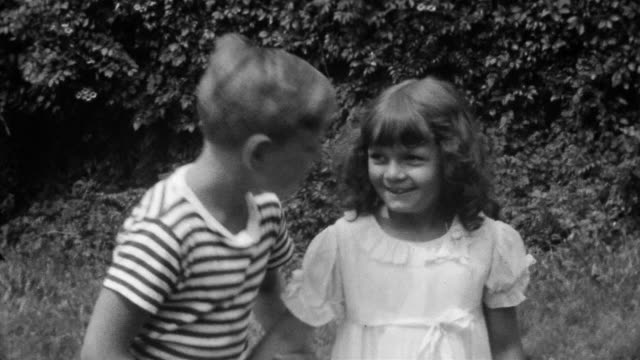 1930s black and white medium shot young boy kissing young girl / laughing - verlieben stock-videos und b-roll-filmmaterial