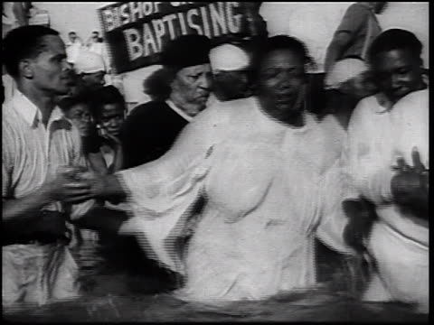 b/w 1930s black minister + assistant baptising 2 black women in waist-deep water - バプテスト点の映像素材/bロール
