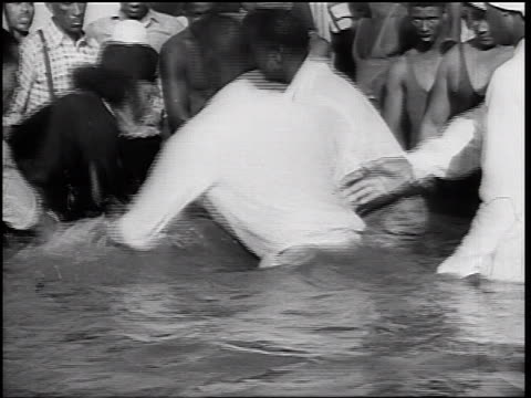 b/w 1930s black minister baptising jumping + shaking black woman in waist-deep water - バプテスト点の映像素材/bロール