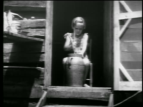b/w 1930s blonde girl sitting in doorway of farm building churning butter / newsreel - butter stock videos and b-roll footage