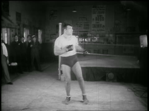 b/w 1930s boxer standing by swinging punching bag after having hit it in gym - primo carnera stock videos and b-roll footage