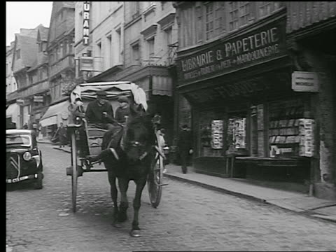 vidéos et rushes de b/w 1930s boy + man driving horse-drawn cart in narrow street with stores / lisieux, normandy, france - 1930