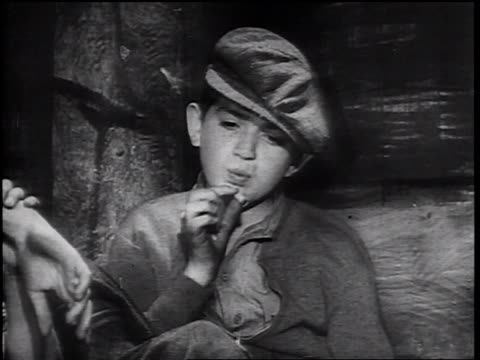 vídeos de stock, filmes e b-roll de b/w 1930s boy with hat smoking cigarette + passing cigarette to 2nd boy - smoking