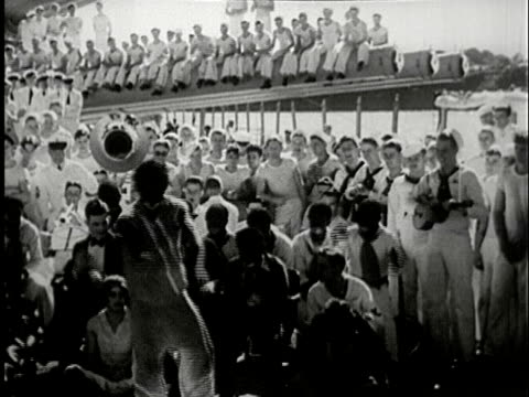 vidéos et rushes de 1930s b/w ms, black american sailor with face painted dancing in front of audience of sailors on ship deck - marin