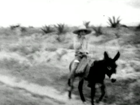 1930s B/W WS PAN Boy with hat riding on back of donkey down dirt path / Mexico
