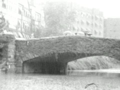 vidéos et rushes de 1930s b/w ws pan bridge during heavy rainfall, water levels under bridge very high, people crossing above with umbrellas / usa - ville moyenne