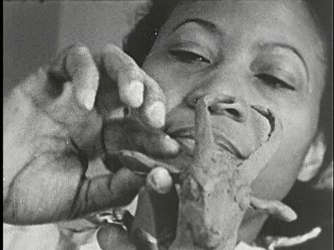 1930s b/w cu, composite, ecu, female artist sculpting  figure of antelope in clay in studio, new york, city, new york state, usa - 小さな像点の映像素材/bロール