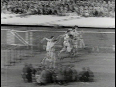 1930s B/W Jesse Owens running hurdles at the British Empire Commonwealth Games / United Kingdom