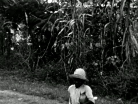 vídeos de stock e filmes b-roll de 1930s b/w montage boy walking toward camera and smiling, view of town with church / haiti - índias ocidentais