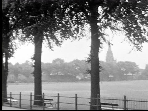 1930s B/W WS pan past park to woman riding bicycle