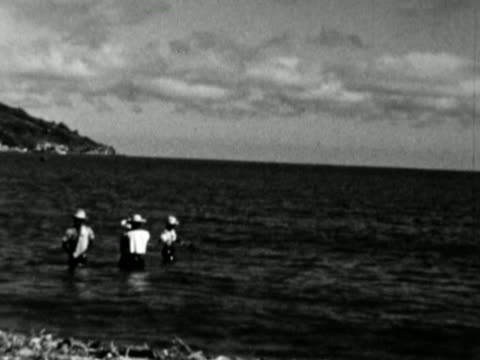 vidéos et rushes de 1930s b/w ws pan people on beach and waist deep in sea / haiti - antilles occidentales