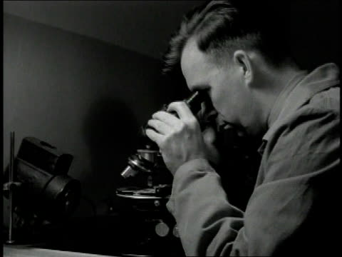 vídeos de stock, filmes e b-roll de 1930s b/w scientist using a microscope - microscópio