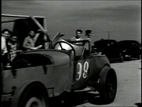 vídeos de stock, filmes e b-roll de 1930s b/w spectators and pit crew watching as hot rod cars drive past / corona show grounds speedway, corona, california, united states - hot rod