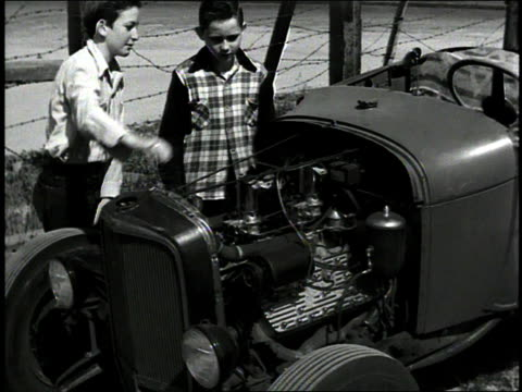 vídeos de stock, filmes e b-roll de 1930s b/w two boys inspecting hot rod car engine / corona show grounds speedway, corona, california, united states - hot rod